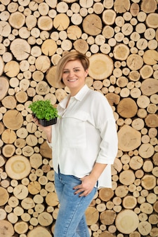 Bella giovane donna che tiene un colore micro-verde su una parete di tronchi di legno.