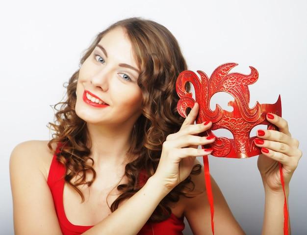 Bella giovane donna che tiene la maschera rossa