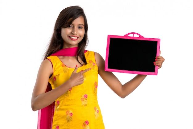 Bella giovane donna che tiene e che mostra qualcosa sulla lavagna o sull'ardesia, isolata su bianco