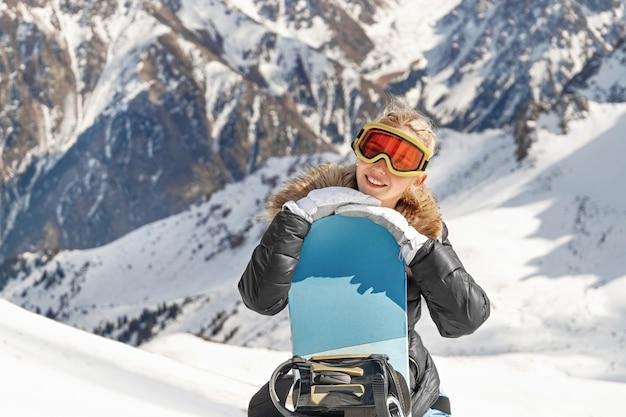 Bella giovane donna che tiene lo snowboard, sta guardando la macchina fotografica e sorride, copia lo spazio.