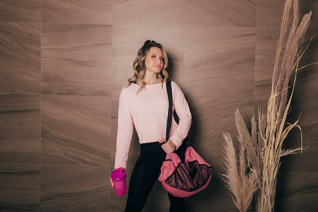 Una bellissima giovane donna con in mano una borsa sportiva e una bottiglia d'acqua