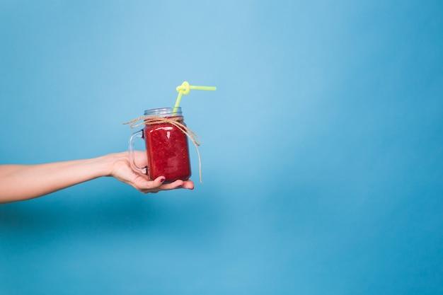 Bella giovane donna che tiene il frullato di fragole sul blu. concetto di bevande organiche sane. persone a dieta.