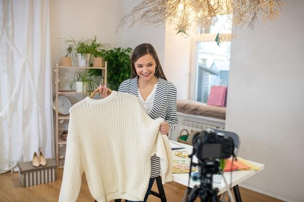 Bella giovane donna che tiene un pullover bianco mentre dà consigli sui vestiti
