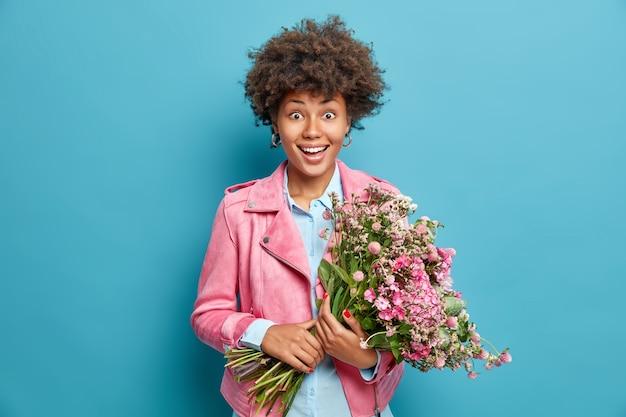 La bella giovane donna tiene il grande mazzo di fiori profumati celebra l'8 marzo vestita in giacca rosa isolata sopra la parete blu