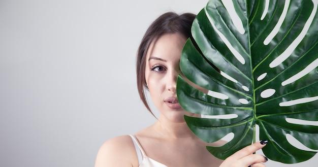 La bella giovane donna tiene una grande foglia verde