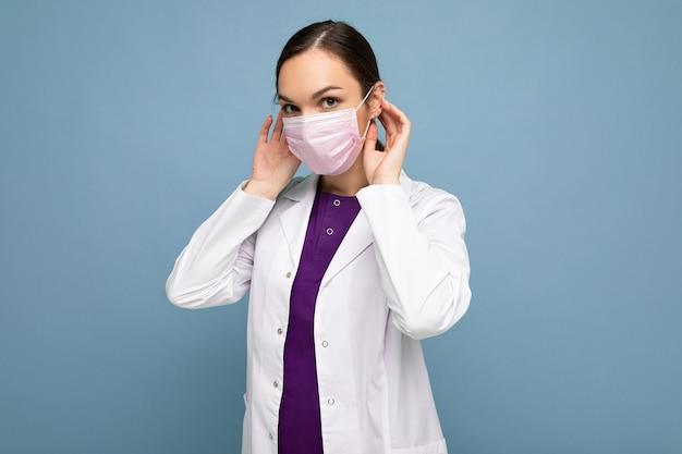 La bella giovane donna tiene e indossa una maschera medica bianca per proteggersi dal virus corona