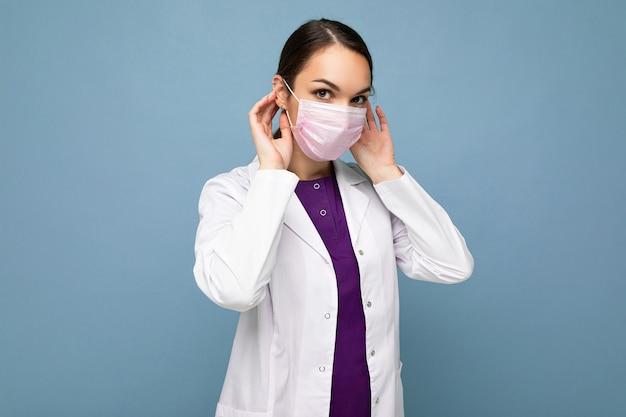 La bella giovane donna tiene e indossa una mascherina medica bianca