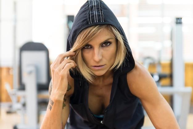Bella giovane donna in una giacca con cappuccio in palestra. donna fitness in abiti sportivi che guarda l'obbiettivo