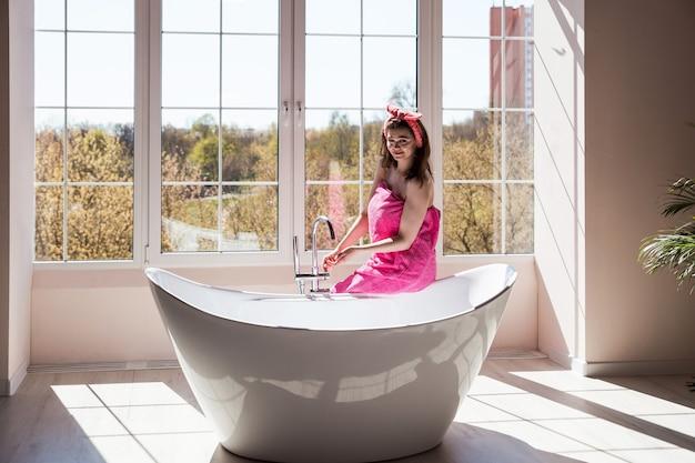 Bella giovane donna sta per fare un bagno in una grande vasca da bagno in ceramica alla moda alla moda