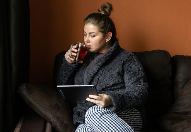 La bella giovane donna sta bevendo il tè e sta usando una compressa. trascorrere del tempo in un accogliente appartamento a casa in inverno durante la quarantena.