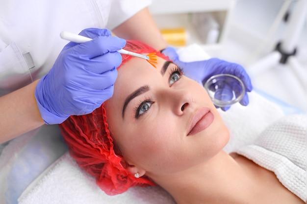 La bella giovane donna sta ricevendo il trattamento della pelle del viso. medico edico con un pennello per applicare un farmaco terapeutico.