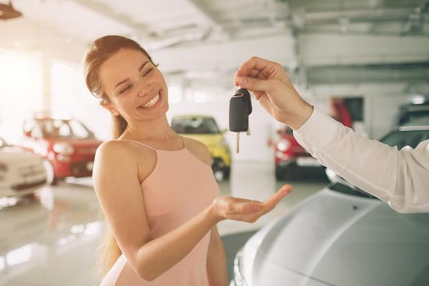 La bella giovane donna sta tenendo una chiave in concessionaria auto. affari automobilistici, vendita di automobili, - modello femminile felice in esposizione o salone di automobile.
