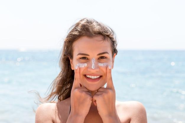 La bella giovane donna sta posando alla macchina fotografica con la crema solare sul viso sullo sfondo del mare.