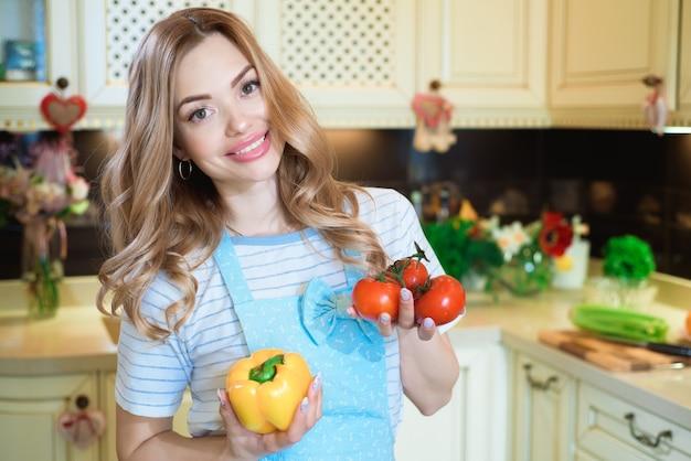 La bella giovane donna sta preparando l'insalata di verdure in cucina. cibo salutare.