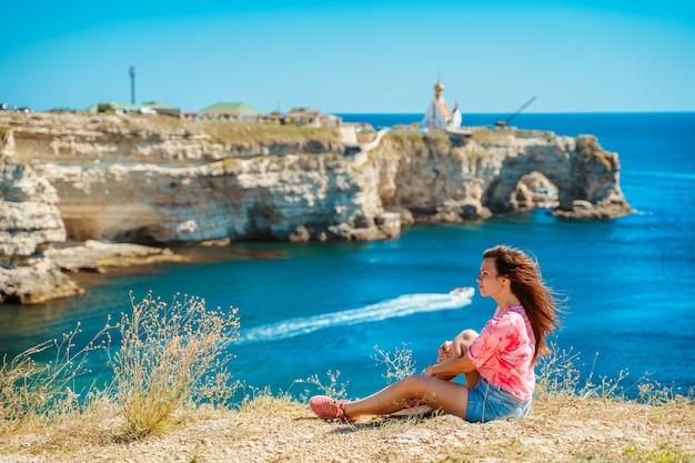 Una bellissima giovane donna è seduta sul bordo di una scogliera e si gode un pittoresco paesaggio marino