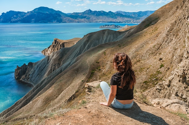 Una bellissima giovane donna è seduta sull'erba con vista sul paesaggio con cape chameleon