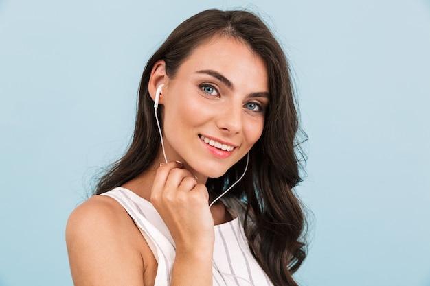 Bella giovane donna isolata musica d'ascolto della parete con gli auricolari.