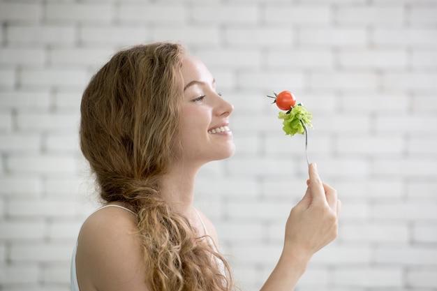Bella giovane donna in posture gioiose con insalata di mano che tiene il folk