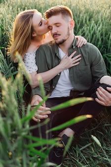 La bella giovane donna bacia suo marito la sera d'estate seduto in campo tra erba alta. amore e tenerezza. bei momenti di vita. giovinezza e bellezza. pace e disattenzione.