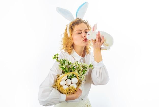 Bella giovane donna che bacia coniglio bianco, ragazza carina il giorno di pasqua, caccia alle uova di pasqua.