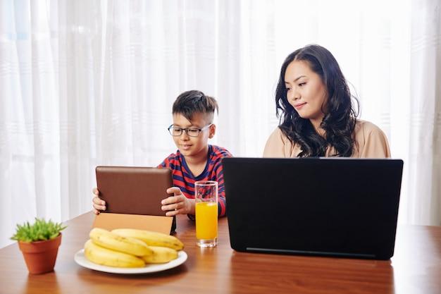 Bella giovane donna al tavolo della cucina che lavora al computer portatile, suo figlio seduto nelle vicinanze e guardare video educativi su tavoletta digitale