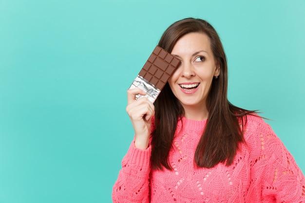 Bella giovane donna in maglione rosa lavorato a maglia che guarda da parte tenere in mano che copre l'occhio con una barretta di cioccolato isolata sul ritratto dello studio del fondo della parete blu. concetto di stile di vita della gente. mock up copia spazio.