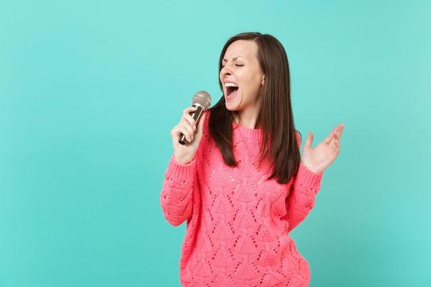 Bella giovane donna in maglione rosa lavorato a maglia con gli occhi chiusi tenendo in mano, canta una canzone nel microfono isolato su sfondo blu muro, ritratto in studio. concetto di stile di vita della gente. mock up copia spazio.