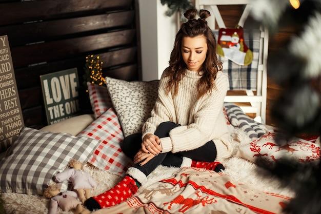 Bella giovane donna in maglione caldo lavorato a maglia e calzini rossi sul letto con decorazioni natalizie