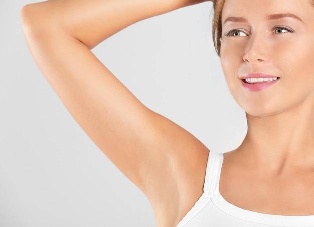 Bella giovane donna sulla luce. concetto di utilizzo del deodorante