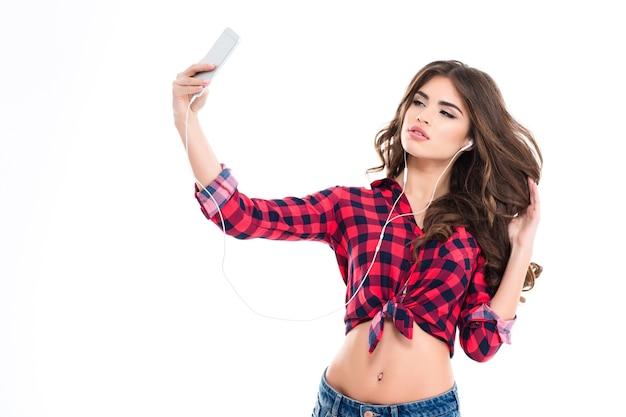 Bella giovane donna che ascolta la musica negli auricolari e fa selfie con lo smartphone sul muro bianco