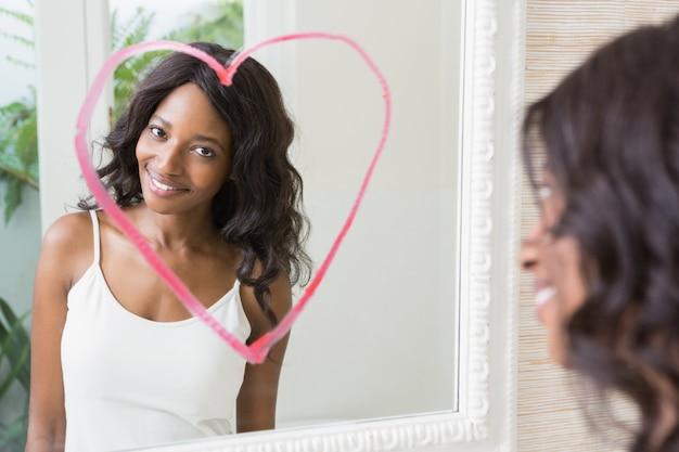Bellissima giovane donna guardarsi allo specchio