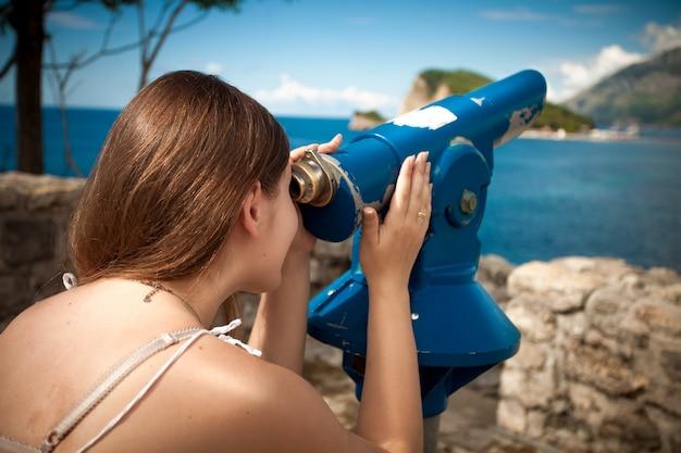Bella giovane donna che guarda la montagna attraverso il telescopio turistico