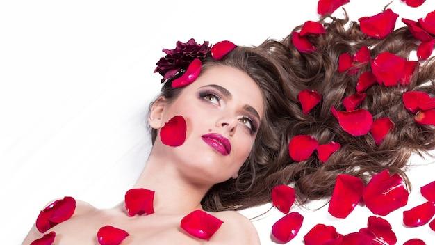 Bella giovane donna sdraiata tra i petali di rosa.