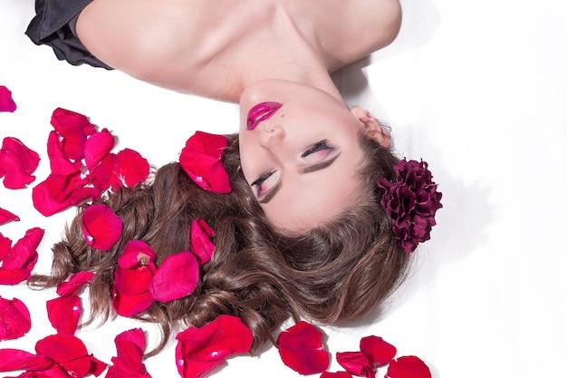 Bella giovane donna sdraiata a letto con petali di rosa. stile di vita e cura del corpo