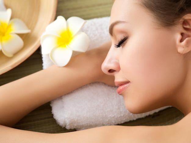 Bella giovane donna sdraiata al salone della stazione termale. cura della pelle e del corpo, stile di vita sano, relax