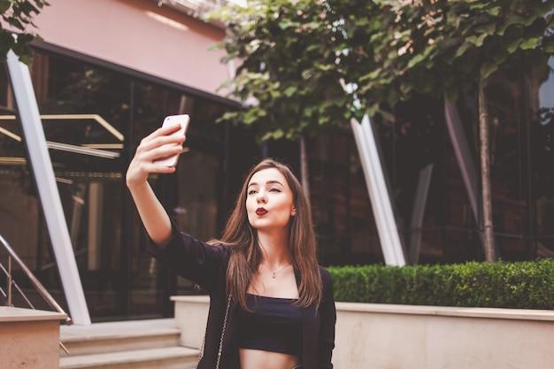 La bella giovane donna fa selfie sullo sfondo di un edificio moderno