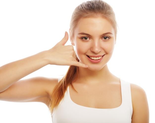 Bella giovane donna che fa una chiamata me gesto, isolato su bianco Foto Premium