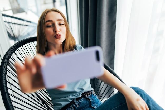 Bella giovane donna che fa selfie con il suo smartphone e sorride mentre è seduta su una grande sedia a casa