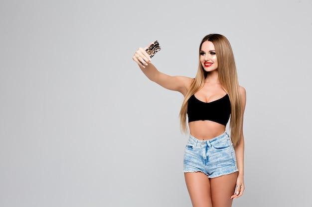 Bella giovane donna che fa selfie scattare foto di se stessa al telefono. ragazza snella in un vestito di jeans con labbra rosse fa una foto di se stessa su uno smartphone.