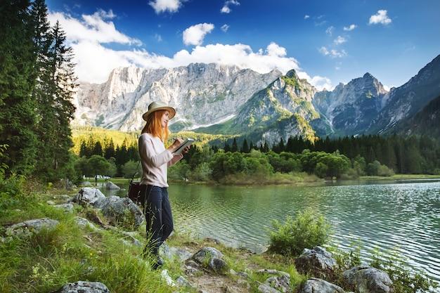Bella giovane donna che fa schizzi o scrive nel suo blocco note sulla natura