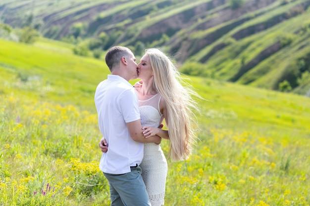 Bella giovane donna e un uomo camminano, si abbracciano e si baciano nella natura al tramonto.
