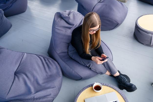 Una bellissima giovane manager è seduta con un telefono su un morbido pouf vicino alla finestra panoramica. imprenditrice al lavoro su un nuovo progetto