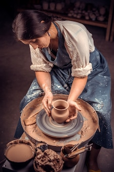 Il maestro di una giovane e bella donna dimostra il processo di realizzazione di piatti in ceramica utilizzando la vecchia tecnologia. lavoro manuale.