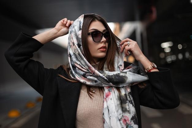 La bella modella della giovane donna in un cappotto nero in occhiali da sole alla moda con le labbra sexy mette sopra una sciarpa di seta elegante alla moda sopra la testa. ragazza attraente moderna di affari del ritratto nella città.