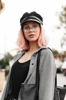 Bella giovane modella con capelli rosa con gli occhiali con una camicia alla moda con un copricapo cammina in città