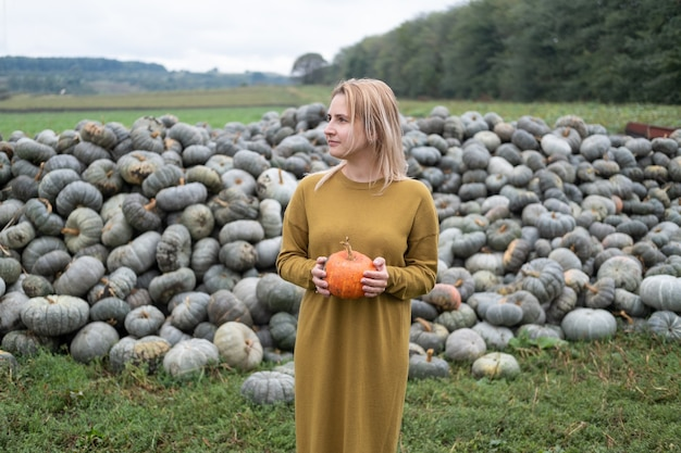 Bella giovane donna in abito di senape con zucca arancione all'aperto sulla toppa. ringraziamento o halloween.