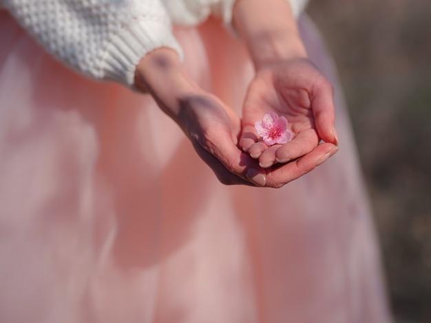 Una bella giovane donna vicino a un albero in fiore di ciliegio primaverile in fiore. l'idea e il concetto di rinnovamento, cura di sé, salute e felicità, mani ravvicinate