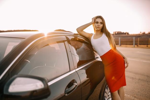 Bella giovane donna vicino a un'auto la sera sotto il sole al tramonto in un parcheggio vuoto