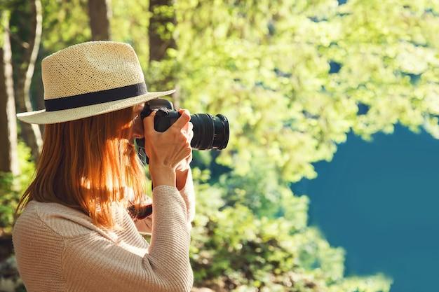 Bello fotografo della giovane donna che prende le immagini sulla macchina fotografica all'aperto sul paesaggio della natura.