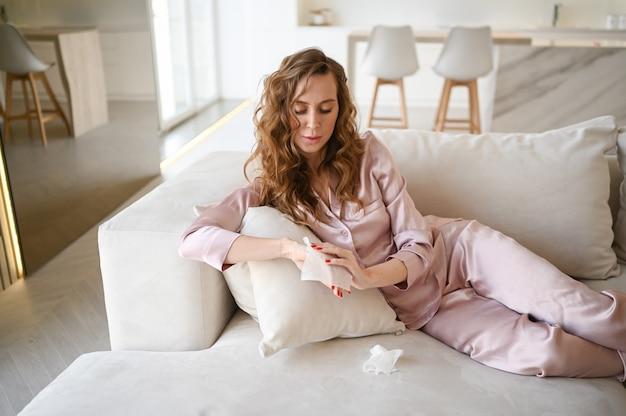 Bella giovane donna in pigiama rosa che pulisce le mani con disinfettante per le mani, usando un batuffolo di cotone con alcool per pulire per evitare di contaminare con il virus corona. igiene per eliminare i germi, pandemia di covid-19